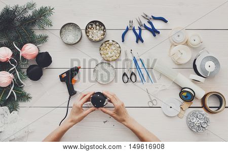 Creative diy hobby. Making handmade craft christmas balls. Woman's leisure, tools for creating holiday decorations, pliers, glue gun and scissors. Top view of white wooden table with female hands.