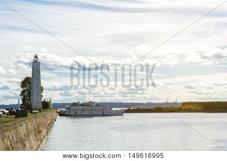 Seaport at sunlight. Lighthouse and navy ship in water bay. Summer landscape cloudy sky.