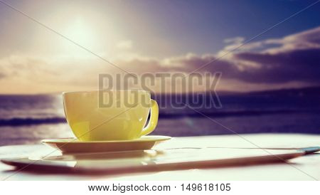 Cup of coffee and tablet pc against ocean against sky during sunset