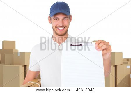 Happy delivery man holding cardboard box and clipboard against arrangements of cardboard boxes