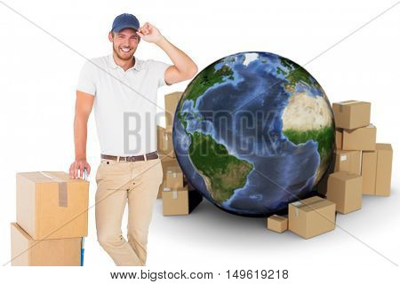 Happy delivery man leaning on trolley of boxes against globe surrounded by cardboard boxes