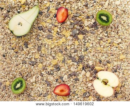 Background out of muesli cereals a mixture of healthy grains cereal flakes and fresh apple plum kiwi and pear.