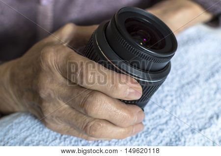 DSLR lens in old woman's hands. Selective focus.