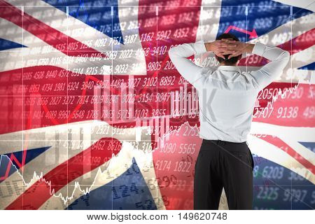 Businessman standing back to the camera with hands on head against digitally generated great britain national flag