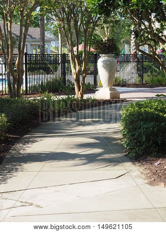 concrete curving sidewalk which is lined with trees. The sidewalk is by a pool area.