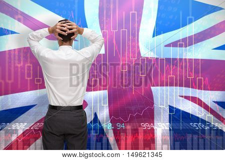 Businessman standing back to camera hands on head against digitally generated great britain national flag