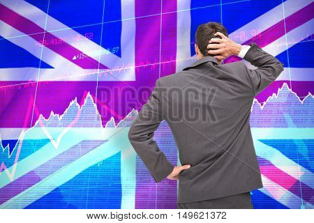Young businessman standing back to camera scratching his head against digitally generated uk national flag