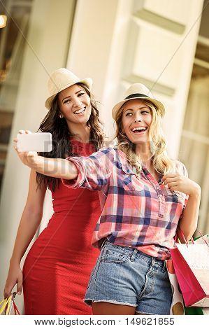 Two girls in shopping having fun. Making selfie.