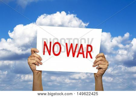 NO WAR card in hand against blue sky with clouds. Selective focus.