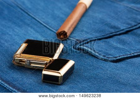 Cigar and lighter lying on a blue denim jacket with space for your text