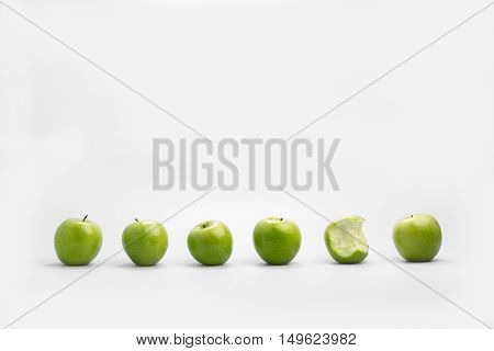 One bitten apple half eaten in a line of whole healthy fresh green apples over a white background with copy space in a conceptual image