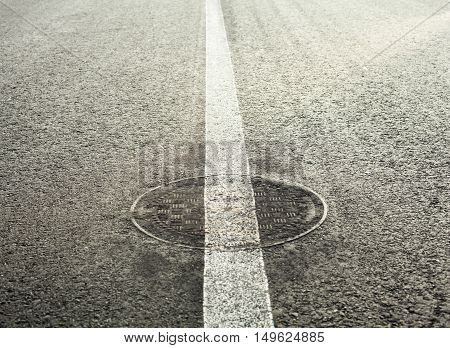 Manhole cover on the road with white road marking line on it.