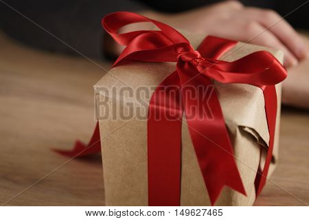 packed gift box with red ribbon and bow, shallow focus