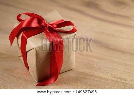 brown paper gift box with red ribbon bow on wooden table, shallow focus