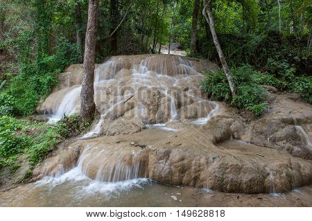 Beautiful Sticky Waterfall In Jungles Of Northern Thailand. Blurred White Waters Of The Waterfall Fl