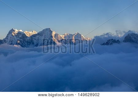 Picturesque Mountain Valley Filled With Curly Clouds At Sunset. Dramatic Snowy Mountain Range Lit Up