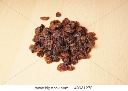 heap of raisins or sultanas on wooden table