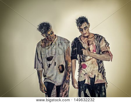 Two male zombies standing on black smoky background, head and shoulder shot