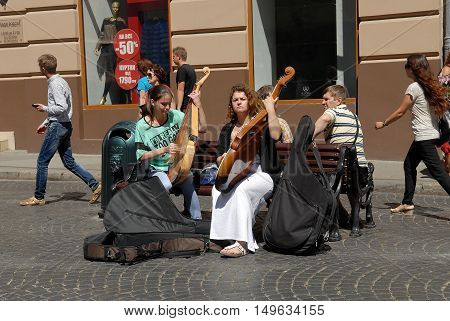 Lvov, Ukraine - July 22, 2016: Street musicians on Market Square one of the most famous and busiest shopping square in Ukraine. Girls playing on bandura. Bandura - ukrainian folk stringed musical instrument.