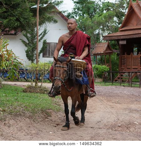Chiang Rai, Thailand - May 21, 2016: Young Buddhist Monk Wearing Traditional Red Robe Riding A Small