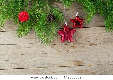 Christmas decor background. The branch of a Christmas tree a pine cone stars on a wooden wall.