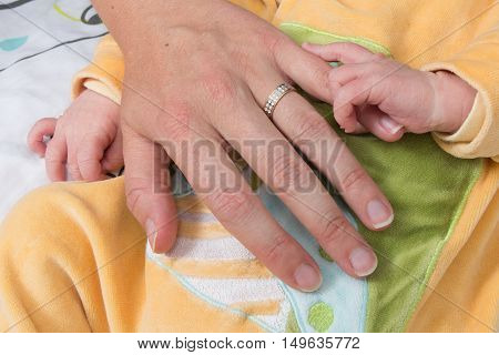 Newborn Baby Grasping Her Mother's Finger. Concept Of Child Care