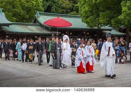 Tokyo Japan - June 5 2016: A traditional Japanese wedding ceremony at Shrine. Wedding parties and family members parade through the inner ground of the Meiji Jingu Shrine.