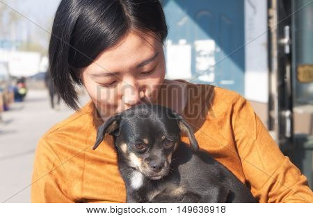 A chinese woman holding and kissing a small calm dog.