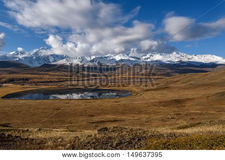 Bright picturesque autumn landscape with beautiful lake in the steppe snow covered mountains and their reflection on a background of blue sky and clouds on a sunny day