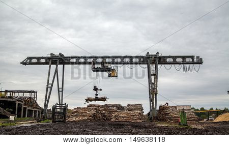 Crane moving a lot of wood at paper manufacturing