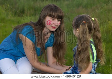 young mom playing with little daughter outdoors
