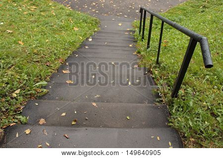 gray stone steps down and a handrail