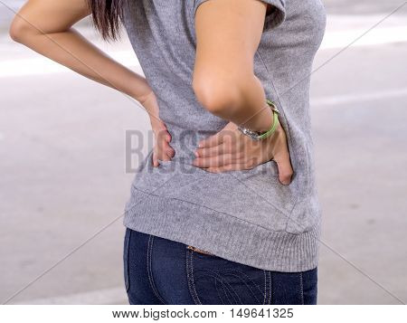 Low Back pain. Woman suffering from painful lumbago or kidney illness.