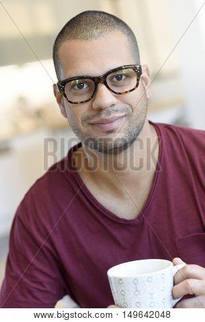 Portrait of hispanic guy with eyeglasses drinking tea