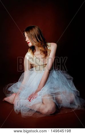 Sad tragic woman sitting on the floor alone in the dark looking away wearing rumples white tulle dress and shiny sequined top