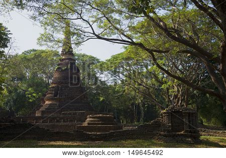 The ancient Chedi of Wat Nang Phaya in the rainforest. Si-Satchanalai, Thailand
