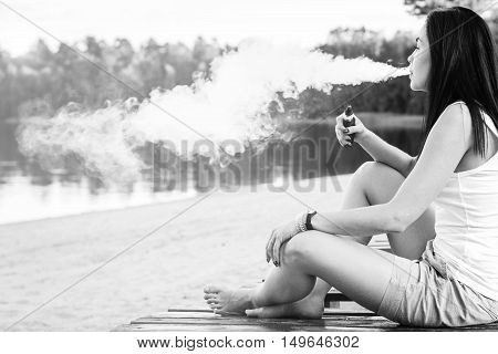 Long Hair Brunette Girl Smoking Electronic Cigarette On The Beach