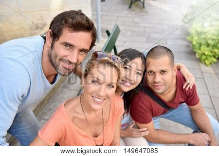 Portrait of four young adults sitting on bench in town