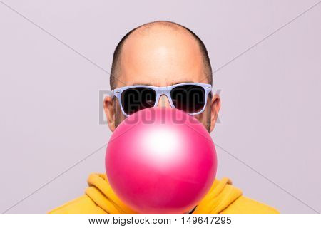 Man with purple sunglasses blowing pink chewing gum and facing the camera