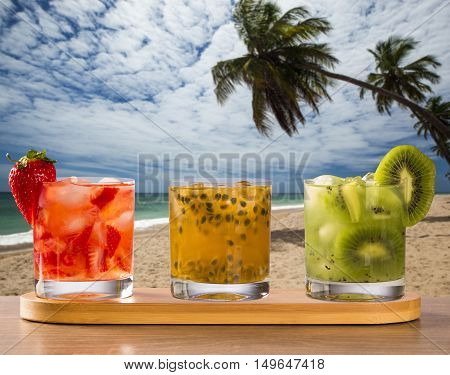 Three Drinks Made With Passion Fruit, Strawberry And Kiwi Caipirinha In The Beach Background