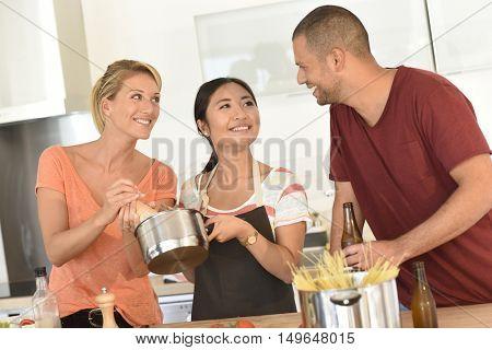Friends having fun preparing dinner together