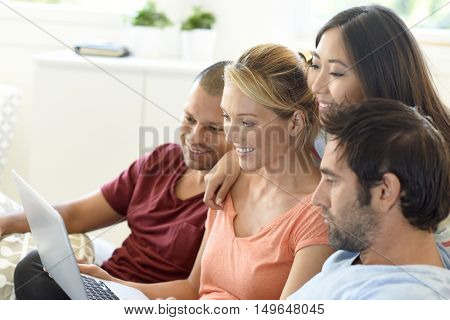 Group of friends sitting in couch websurfing on internet