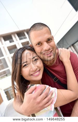 Mixed-race couple embracing each other in town
