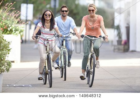 People on vacation riding bicycles in town street