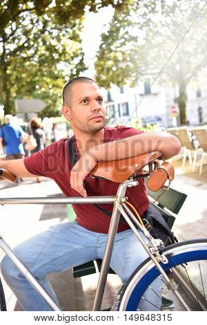 Man waiting in park with bicycle