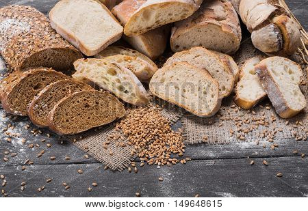 Plenty of sliced bread background. Bakery and grocery concept. Fresh, healthy whole grain sliced sorts of rye and white loaves, sprinkled flour on rustic wood table, food closeup.