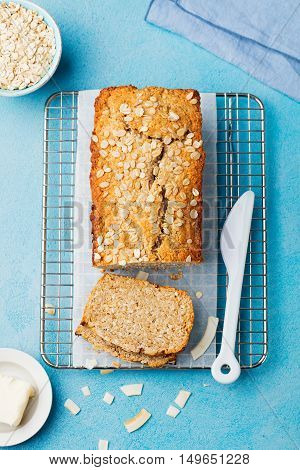 Healthy vegan oat and coconut loaf bread, cake on a cooling rack Blue stone background. Top view