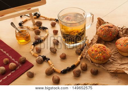 Chinese beautiful flower green tea set with fresh just baked cupcakes made with nuts and chocolate standing on wooden table. Close Up of healthy asian popular jasmine tea.