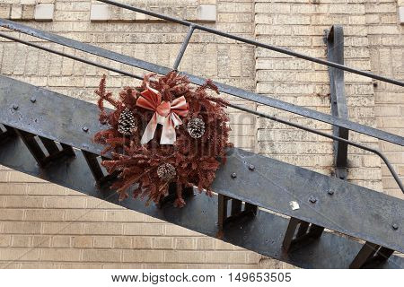 A dried Christmas wreath hanging on a fire escape