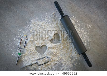 Baking concept on dark background. Baking preparation top view of variety of baking utensils with different kind of flour. Top view. with hearts